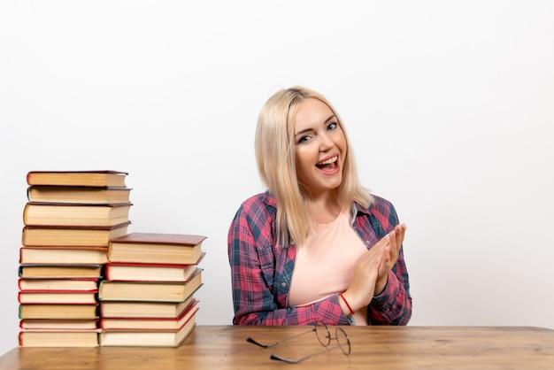 Studentessa seduta con diversi libri su bianco