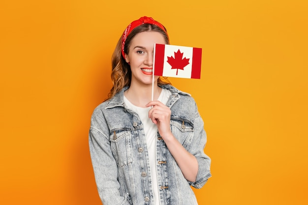 Female student smiling and cover half of her face with a small canada flag isolated over orange wall.
