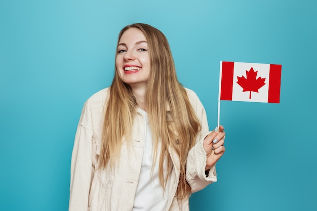 Female student smiling and holding a small canada flag