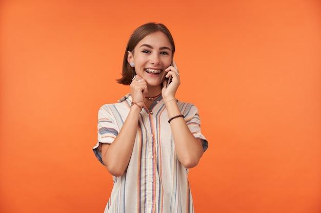 스트라이프 셔츠, 치아 교정기 및 팔찌를 착용하고 스마트 폰으로 이야기를 웃고있는 여학생은 좋은 소식을 듣습니다.