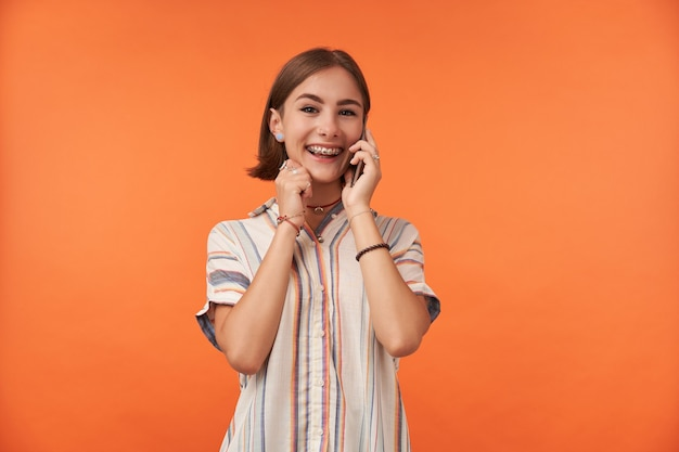 Studentessa sorridente parla su smart phone, indossa una camicia a righe, bretelle e braccialetti per i denti, ascolta una buona notizia.