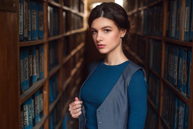 本棚の間に立っている女子学生。