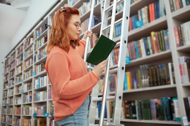 Female student standing on the ladder at the library, reading a book