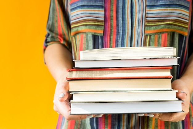 A female student in a striped shirt is holding a stack of textbooks in her hands