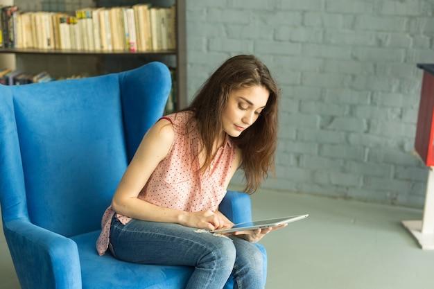 椅子の上の学校図書館で女子学生の研究
