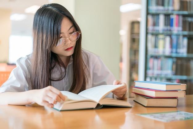 Ученица учится в школьной библиотеке
