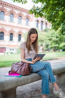Female student studying in a park in front of the school