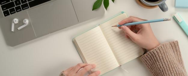 女子学生が研究テーブルのラップトップで割り当てをしながら空白のノートにメモを取る