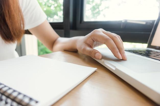 女性の学生が図書館の本からメモを取っています。若いアジア人の女性は、大学の図書館で課題を行うテーブルに座っています。ヴィンテージエフェクトスタイルの写真。