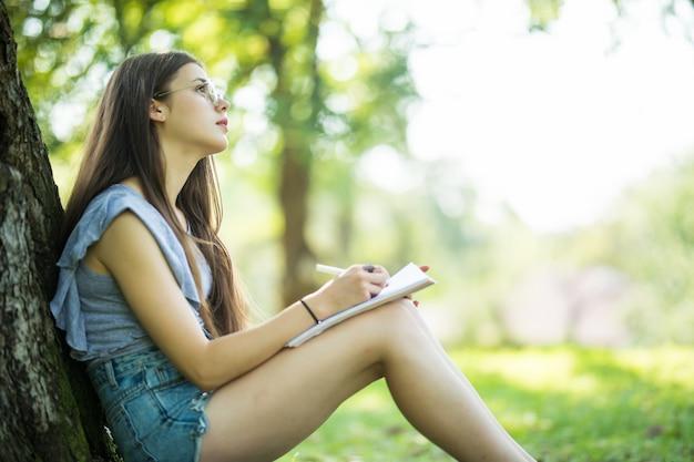 ノートにメモを取る女子学生。割り当てを行う公園に座っている若い笑顔の女性。キャンパスライフ、教育、インスピレーションのコンセプト