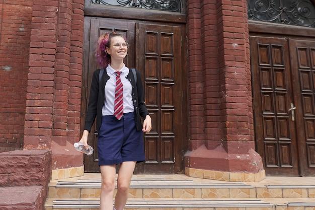 Студентка-подросток в форме с рюкзаком, здание школы фон. снова в школу, обратно в колледж, образование, подростковая концепция