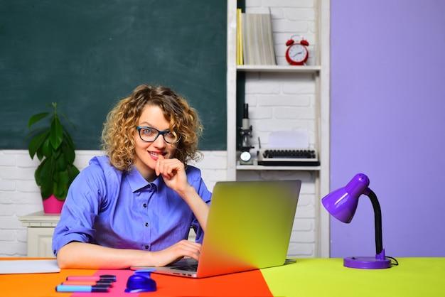 女子学生が教室で大学の若い幸せな学生の先生の授業について考える