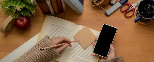 女子学生がスマートフォンを使用して本を読みながら勉強台で試験の準備をする
