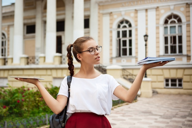 Female student wearing glasses holding tablet and notebooks in different hands outdoors.