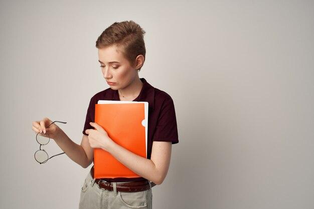 手にオレンジ色のフォルダーと明るい背景を持つ女子学生
