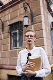 Студентка с книгами возле здания на открытом воздухе, образование, наука, модель
