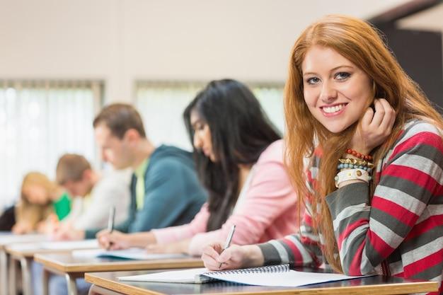 Студентка с другими, записывающая заметки в классе