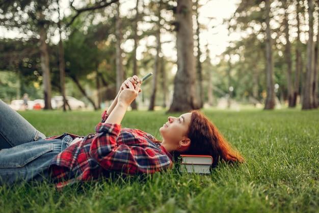 夏の公園の芝生の上に横たわっている電話を持つ女子学生。赤毛のティーンエイジャーの勉強と屋外でのレジャー