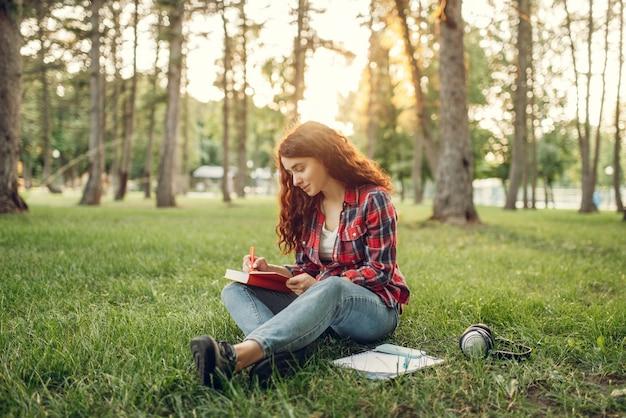 夏の公園の芝生の上でノートに書いている女子学生。生姜ティーンエイジャーの勉強と屋外でのレジャー