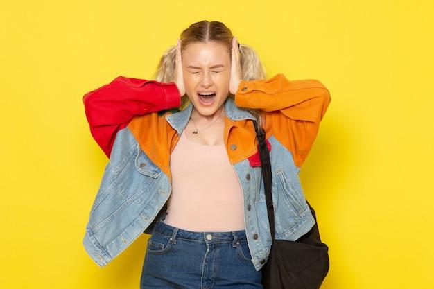黄色の彼女の耳をカバーする現代の服の若い女子学生