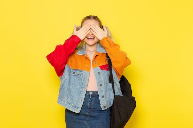 黄色に彼女の目を覆っている現代の服の若い女子学生