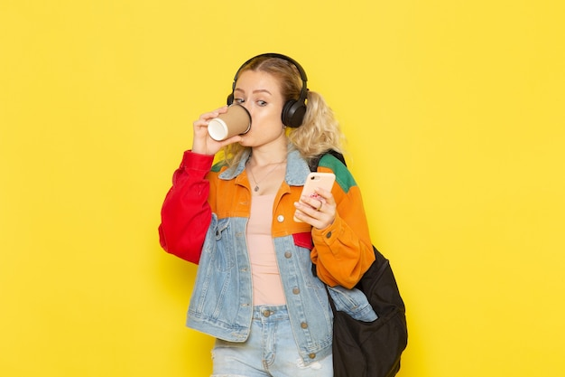 黄色の電話を使用してコーヒーを飲む現代の服の若い女子学生