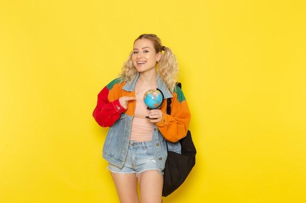 黄色の笑顔で地球を保持している現代の服の若い女子学生