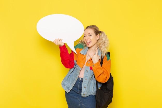 黄色の巨大な白い看板を持っている現代の服の若い女子学生