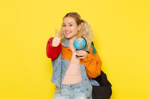 黄色に笑みを浮かべて小さな地球を保持している現代の服の若い女子学生