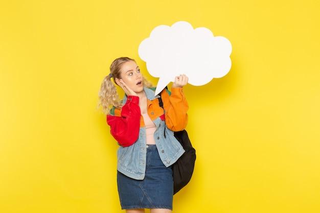 黄色の白い大きな看板を持っている現代の服の若い女子学生