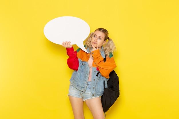 黄色の大きな白い看板を持っている現代の服の若い女子学生