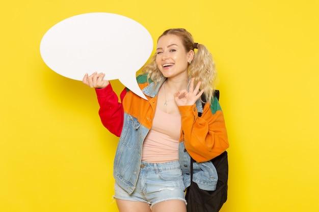 黄色に笑みを浮かべて大きな白い看板を持っている現代の服の若い女子学生