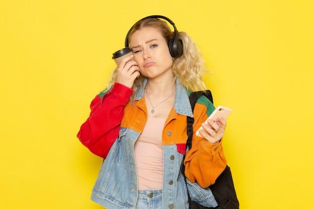 黄色のコーヒーと電話を保持している現代の服の若い女子学生