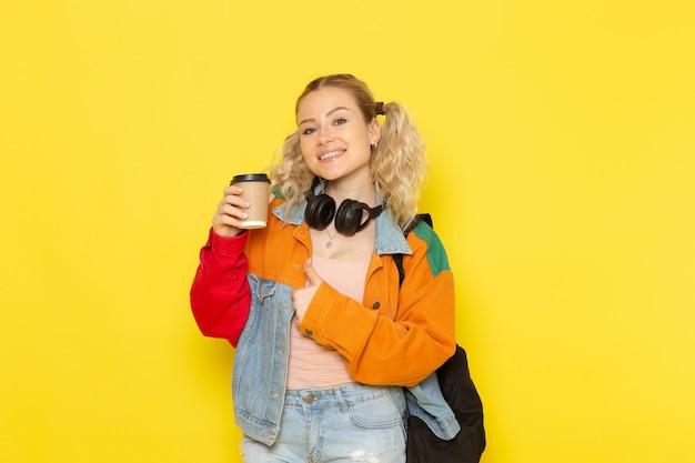 女子学生のコーヒーを押しながら黄色に笑みを浮かべて現代の服の若い