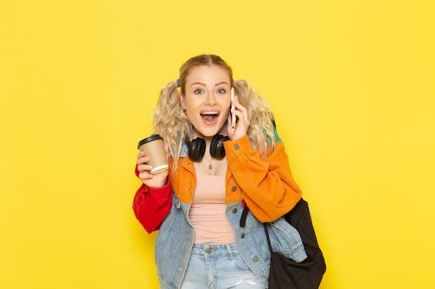 コーヒーを押しながら黄色の電話で話している現代の服の若い女子学生