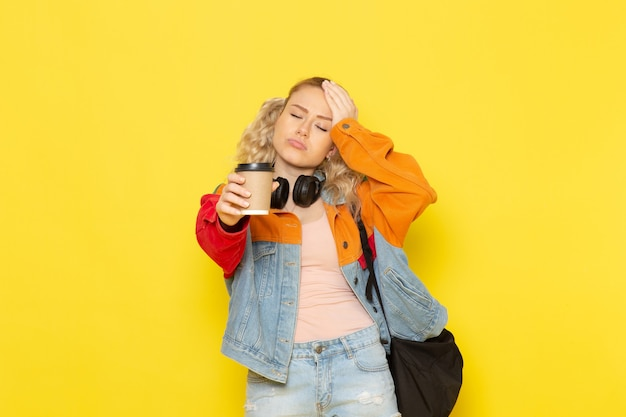 黄色のコーヒーを保持している現代の服の若い女子学生