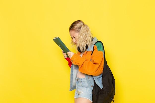 黄色のコピーブックを保持している現代の服の若い女子学生