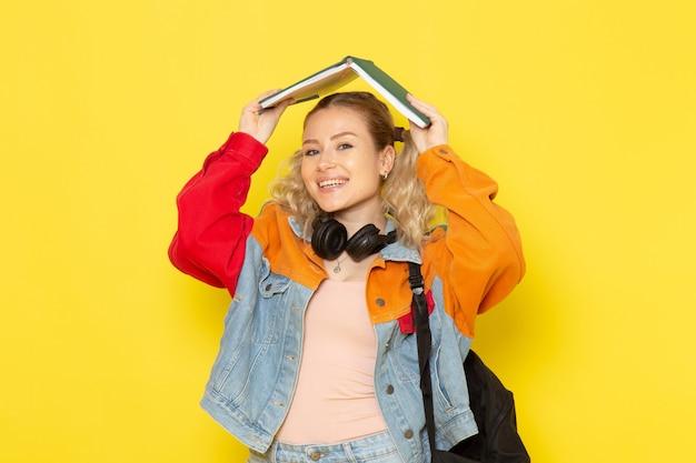黄色に笑みを浮かべてコピーブックを保持している現代の服の若い女子学生