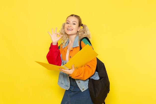 ファイルを保持していると黄色に笑みを浮かべて現代の服の若い女子学生