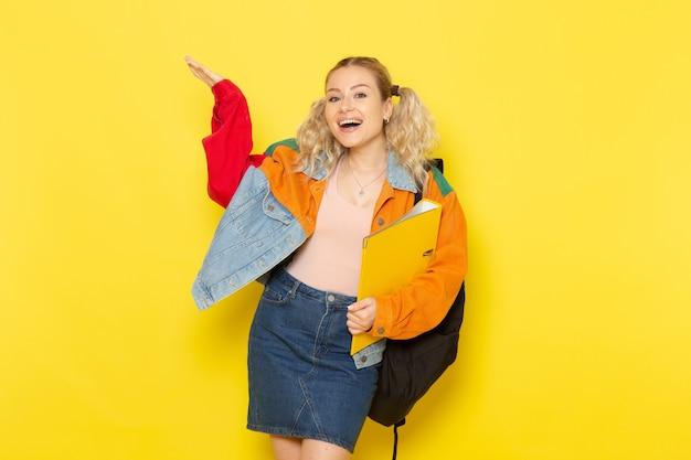 黄色に笑みを浮かべてファイルを保持している現代の服の若い女子学生