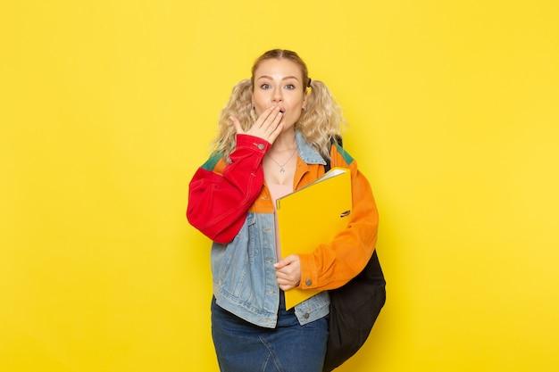 Студентка молодая в современной одежде держит файлы на желтом