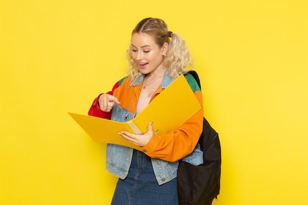 Студентка молодая в современной одежде держит файлы, читая их на желтом