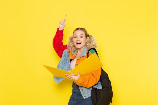 Студентка молодая в современной одежде держит файлы, улыбаясь на желтом