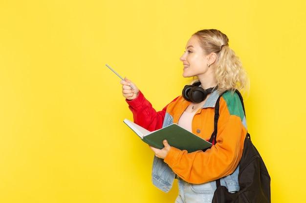 Студентка молодая в современной одежде держит зеленую тетрадь на желтом