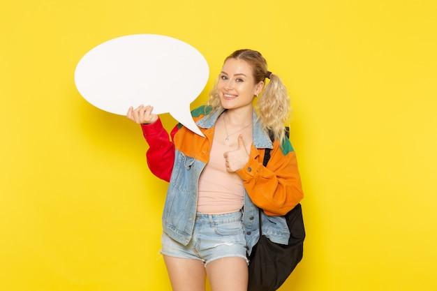 Студентка молодая в современной одежде держит огромный белый знак на желтом