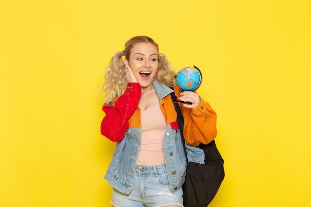 Студентка молодая в современной одежде держит маленький глобус с улыбкой на желтом
