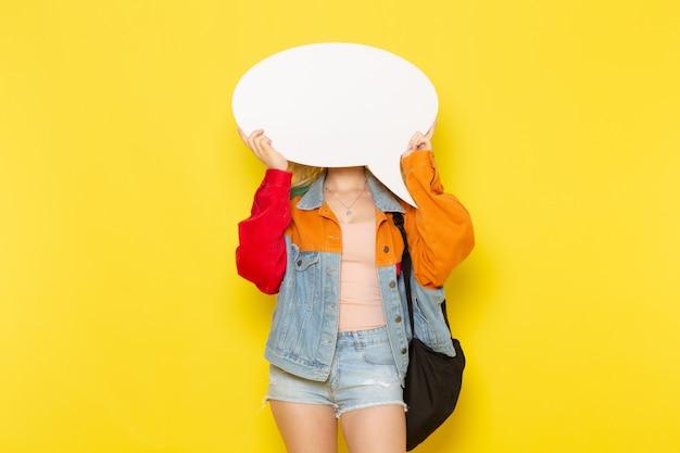 黄色の白い看板を持っている現代の服の若い女子学生