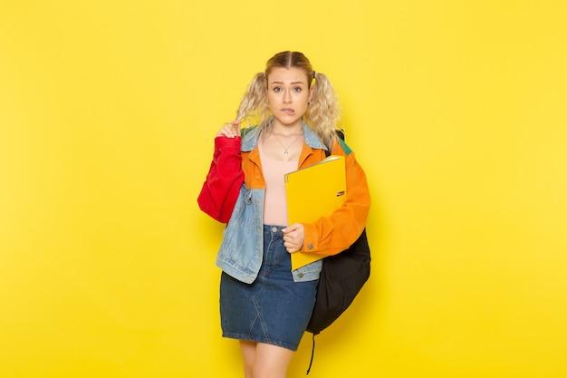 Студентка молодая в современной одежде держит желтые файлы, просто позирует на желтом