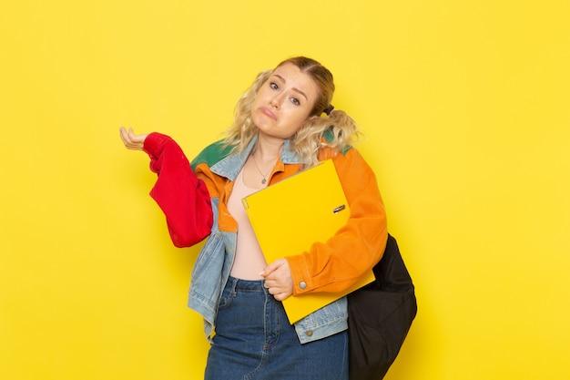 Студентка молодая в современной одежде держит желтые файлы, позирует на желтом