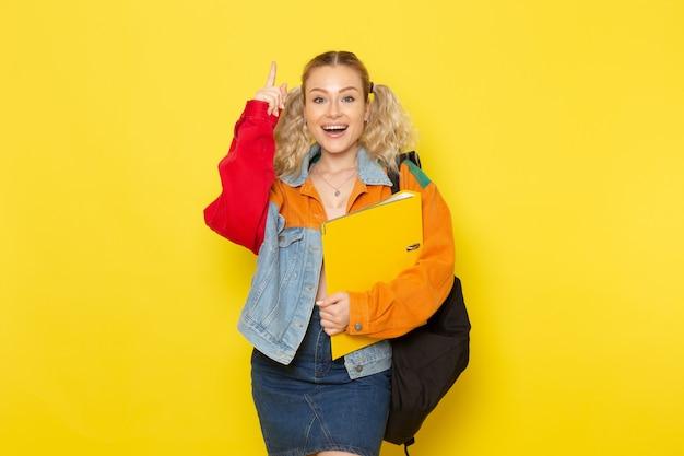 Студентка молодая в современной одежде держит желтые файлы, улыбаясь на желтом